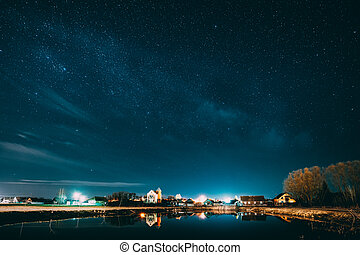 Belarus, Eastern Europe. Night Sky Stars Above Countryside Landscape With Lake Coast And Small Town Or Village. Natural Starry Sky Above Pond And Houses In Early Spring Night