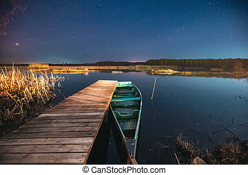 Belarus, Eastern Europe. Real Night Sky Stars Above Old Pier With Moored Wooden Fishing Boat. Natural Starry Sky And Countryside Landscape With Lake River In Early Spring Night. Russian Nature