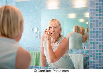beleza feminina, mulher velha, aplicando creme, ligado, rosto, casa