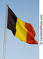 belgian flag on a pole against blue sky