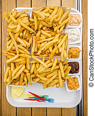 Belgian fries with sauces, french fries and salt packets on tray