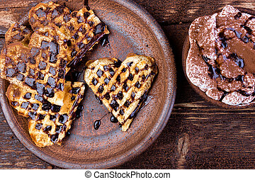 Belgian heart shaped waffle  on brown plate, with hot chocolate with marshmallow on wooden background.