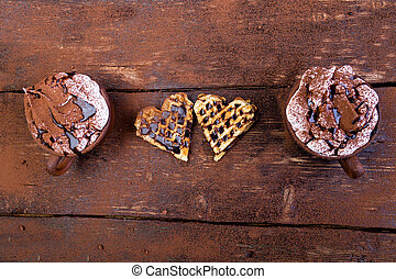 Belgian heart shaped waffle with hot chocolate with marshmallow on wooden background.