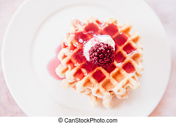 Belgian waffle with plum jam on the white plate