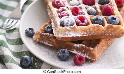 Belgian waffles on plate with berries. Sweet waffle breakfast. Dessert served on table with napkin and fork.