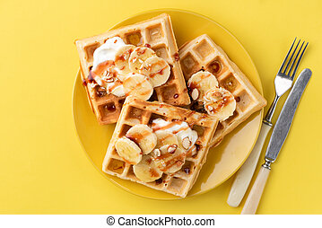 Belgian waffles with banana, caramel sauce and almonds