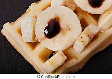 Belgian waffles with banana slices and chocolate sauce.