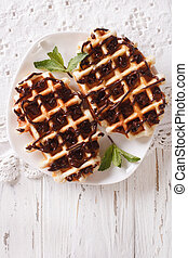 Belgian waffles with chocolate on a plate close-up. vertical...