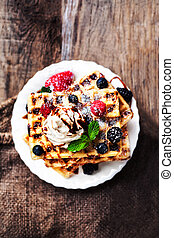 Belgian waffles with ice cream and berry fruits on wooden background, homemade healthy breakfast