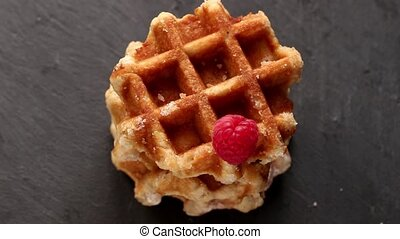 Belgian waffles with raspberries and sugar powder over rusty...