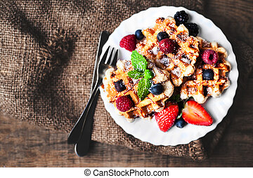 Belgian waffles with strawberries, blueberries and syrup on wooden table