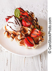 Belgian waffles with strawberries, whipped cream and chocolate close-up. vertical