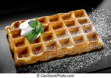 Belgium waffle with mint on black plate