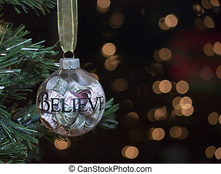 """Glass Christmas tree ornament with the word """"Believe"""" written on it."""