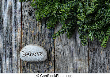 Believe in Christmas with Pine Needles on Rustic Wood Background