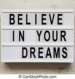 'Believe in your dreams' word on lightbox over white wooden background, view from above. Flat lay, top view, overhead.