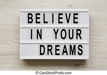 'Believe in your dreams' word on modern board over white wooden background, top view. Flat lay, from above, overhead.