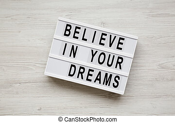 'Believe in your dreams' word on modern board over white wooden surface, top view. Flat lay, from above, overhead.