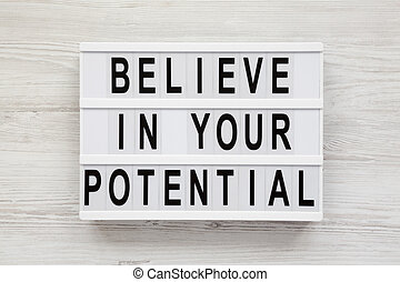 'Believe in your potential' words on a light box on a white wooden background, top view. Flat lay, overhead, from above.