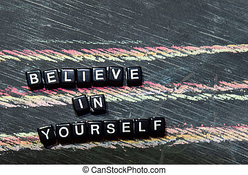 Believe in Yourself on wooden blocks. Cross processed image with blackboard background. Inspiration, education and motivation concepts with The words subject of this image is not in focus.