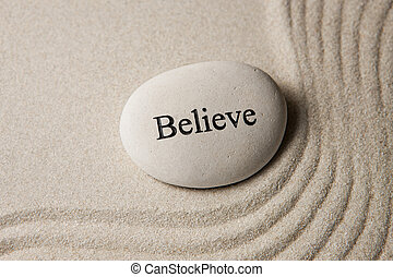 Believe - Inspirational stone surrounded by sand ripples....