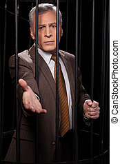 Believe me! Frustrated senior man in formalwear standing behind a prison cell and stretching out hand while isolated on black background