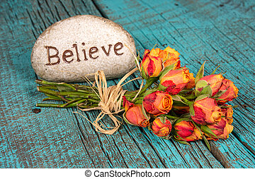believe sign on rock with rose bouquet