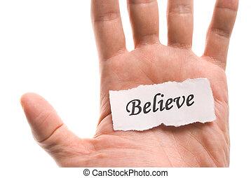 Believe word in hand, word on piece tear paper