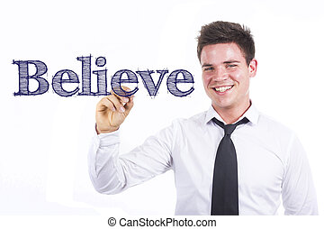 Believe - Young smiling businessman writing on transparent surface