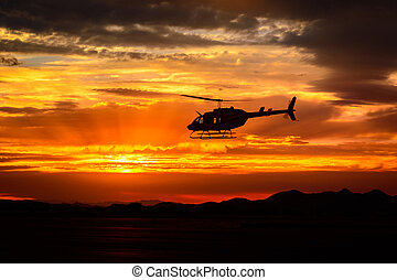 Bell 206 sunset - Bell 206 helicopter flying into the...
