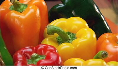 XCU of yellow bell pepper zoom out to CU of wicker basket filled with variety of bell peppers