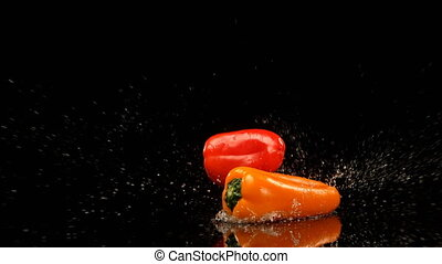Bell peppers falling on water against black background 4k - ...