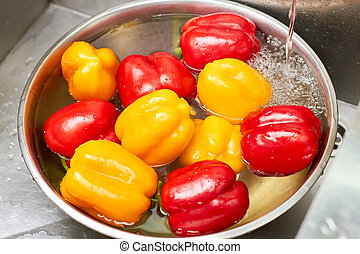 Bell peppers washing in metal bowl with water.
