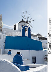 Bell tower in Oia with a windmill in the background, Santorini