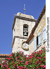 Bell tower of the church Saint Vincent from Gourdon in France with Nerium oleander flower in the foreground, department Alpes Maritimes