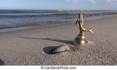 bell with mermaid figure on beach