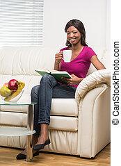 bella donna, seduta, divano, rilassato, interno, giovane, book., casa ritratto, lettura ragazza, sorridente