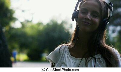 belle femme, écouteurs, jeune, musique, dehors, apprécie