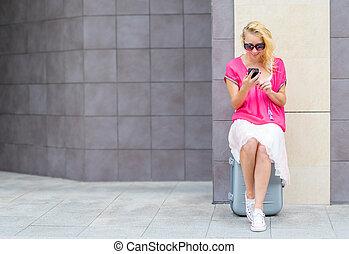 belle femme, asseoir, montre, téléphone, valise