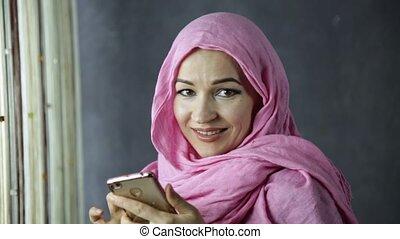 belle femme, conversation, musulman, téléphone, fenêtre, devant