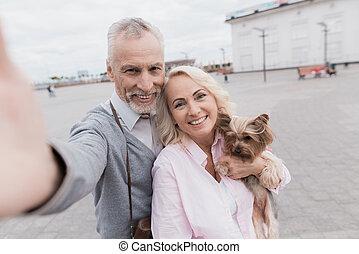 belle femme, elle, square., couple, chien, personnes agées, tenant mains, petit, marques, selfie