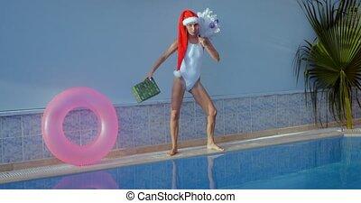 belle femme, jeune, santa chapeau, piscine, natation
