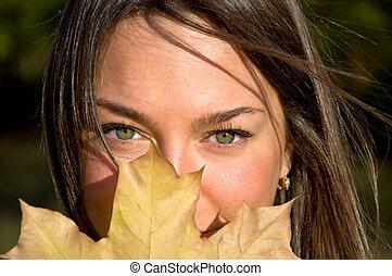 belle femme, leaf., jeune, automne, appareil photo, portrait., regarde, tenue, eyes., vert, érable