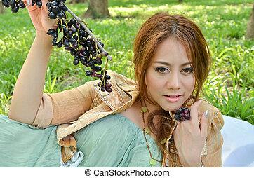 belle femme, parc, manger, fruit