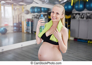 belle femme, serviette, tenue, pregnant, gymnase, bouteille, sourire