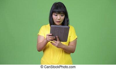belle femme, tablette, regarder, asiatique, numérique, utilisation, surpris, heureux