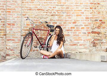 belle femme, vieux, mur, -, bike-phone, devant, brique, rouges