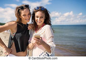 belles filles, regarder, téléphone, sourire, plage