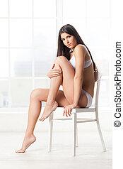 belleza, en, lingerie., atractivo, mujer joven, en, lenceria, sentado, en, el, silla, y, mirar cámara del juez