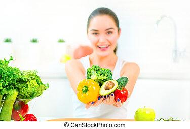 belleza, mujer joven, tenencia, verduras frescas, y, fruits, en, ella, cocina, en, home., el comer sano, concepto